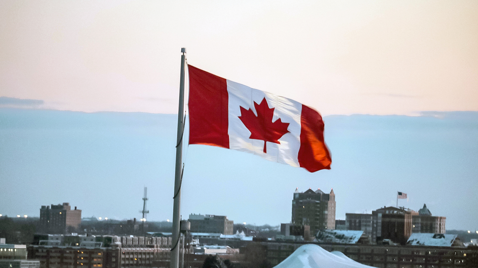 A Canadian flag flying atop city buildings